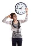Νέοι ασιατικοί αντίχειρες επιχειρησιακών γυναικών κάτω με ένα ρολόι Στοκ Φωτογραφίες