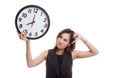 Νέοι ασιατικοί αντίχειρες επιχειρησιακών γυναικών κάτω με ένα ρολόι Στοκ Εικόνα