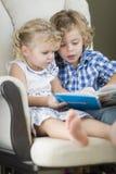 Νέοι αδελφός και αδελφή που διαβάζουν ένα βιβλίο από κοινού στοκ εικόνες με δικαίωμα ελεύθερης χρήσης