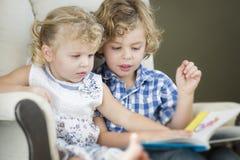 Νέοι αδελφός και αδελφή που διαβάζουν ένα βιβλίο από κοινού στοκ εικόνα