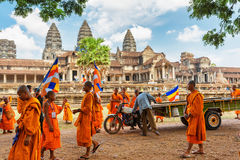 Νέοι βουδιστικοί μοναχοί με τις σημαίες σε αρχαίο Angkor Wat, Καμπότζη Στοκ Φωτογραφία