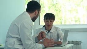 Νέοι γιατροί που εργάζονται με ένα lap-top σε ένα γραφείο απόθεμα βίντεο