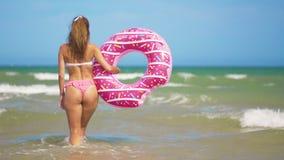 Νέοι γλουτοί γυναικών που περπατούν στη θάλασσα με ρόδινο διογκώσιμο doughnut φιλμ μικρού μήκους