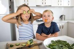 Νέοι γλυκοί αμφιθαλείς που παίζουν με την κουζίνα αγγουριών και καρότων στο σπίτι στον τρόπο ζωής αδελφών και αδελφών Στοκ Εικόνα