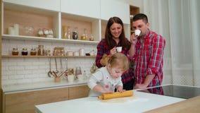 Νέοι γονείς και κόρη μικρών παιδιών που έχει τη διασκέδαση μαζί στην κουζίνα απόθεμα βίντεο
