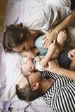 Νέοι γονείς με τα μικρά παιδιά που βρίσκονται στο κρεβάτι Στοκ Εικόνες
