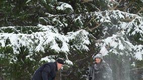 Νέοι γυναίκα και άνδρας που ρίχνουν το χιόνι επάνω απόθεμα βίντεο