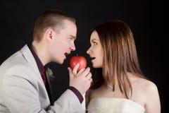 Νέοι γυναίκα και άνδρας εραστών που δαγκώνουν ένα μήλο στοκ εικόνες