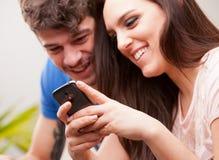 Νέοι γυναίκα και άνδρας με ένα κινητό τηλέφωνο Στοκ Εικόνες