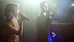 Νέοι ελκυστικοί άνδρας και γυναίκα που χορεύουν και που τραγουδούν με  φιλμ μικρού μήκους