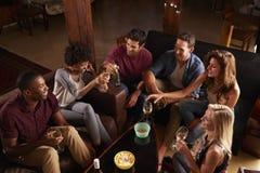 Νέοι ενήλικοι που κοινωνικοποιούν σε ένα κόμμα στο σπίτι, ανυψωμένη άποψη στοκ φωτογραφία