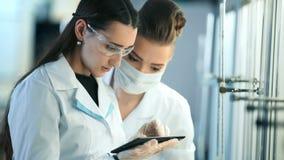 Νέοι επιστήμονες με το PC ταμπλετών που κάνουν τη δοκιμή ή την έρευνα στο κλινικό εργαστήριο απόθεμα βίντεο