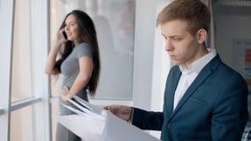 Νέοι επιτυχείς επιχειρηματίες στη διαδικασία εργασίας στο σύγχρονο εσωτερικό της επιχείρησης απόθεμα βίντεο