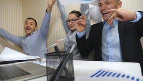 Νέοι επιχειρηματίες που γιορτάζουν το επίτευγμα που ρίχνει επάνω στα έγγραφα και που παρουσιάζει χαρούμενες συγκινήσεις arms back φιλμ μικρού μήκους