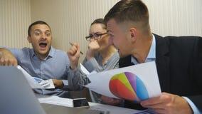 Νέοι επιχειρηματίες που γιορτάζουν το επίτευγμα που ρίχνει επάνω στα έγγραφα και που αυξάνει τα χέρια Εργαζόμενοι γραφείων που χα απόθεμα βίντεο