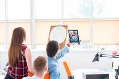 Νέοι επιχειρηματίες που παίρνουν ένα selfie στο γραφείο με την ταμπλέτα στοκ εικόνα
