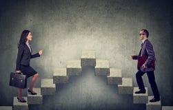 Νέοι επιχειρησιακοί γυναίκα και άνδρας που επιταχύνουν μια σκάλα σταδιοδρομίας κλιμακοστάσιων Στοκ Φωτογραφίες