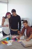 Νέοι επιχειρησιακοί συνάδελφοι που συζητούν στο γραφείο γραφείων Στοκ Φωτογραφία