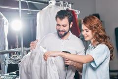 νέοι εργαζόμενοι στεγνού καθαρισμού που ανιχνεύουν το γραμμωτό κώδικα στην τσάντα στοκ εικόνες