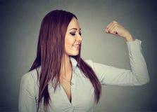 Νέοι ευτυχείς μυ'ες κάμψης γυναικών που παρουσιάζουν δύναμή της στοκ φωτογραφία