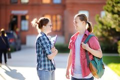 Νέοι ευτυχείς σπουδαστές με τα βιβλία και σημειώσεις στη πανεπιστημιούπολη Στοκ εικόνες με δικαίωμα ελεύθερης χρήσης
