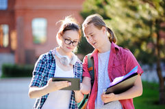 Νέοι ευτυχείς σπουδαστές με τα βιβλία και σημειώσεις στη πανεπιστημιούπολη Στοκ φωτογραφία με δικαίωμα ελεύθερης χρήσης