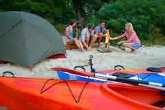 Νέοι ευτυχείς ταξιδιώτες που στηρίζονται στο βράδυ με την πυρκαγιά στην παραλία άμμου κοντά στα καγιάκ και τη σκηνή Στοκ Φωτογραφία