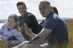 Νέοι ευτυχείς φίλοι που κάθονται στη χλόη που απολαμβάνει την αναψυχή μαζί υπαίθρια στοκ φωτογραφίες