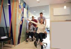 Νέοι εύθυμοι επιχειρηματίες στην έξυπνη περιστασιακή ένδυση που έχει τη διασκέδαση συναγωνιμένος στις καρέκλες και το χαμόγελο γρ Στοκ φωτογραφίες με δικαίωμα ελεύθερης χρήσης