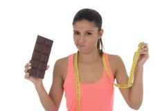 Νέοι ελκυστικοί λατινικοί taylor εκμετάλλευσης γυναικών ταινία μέτρου και φραγμός σοκολάτας στην υγιεινή διατροφή διατροφής Στοκ φωτογραφία με δικαίωμα ελεύθερης χρήσης