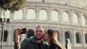 Νέοι ελκυστικοί γυναίκα και άνδρας που στέκονται κοντά στο Colosseum στη Ρώμη, Ιταλία Το ζεύγος παίρνει τη φωτογραφία selfie στο  στοκ φωτογραφία με δικαίωμα ελεύθερης χρήσης