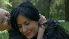 Νέοι ελκυστικοί μητέρα και γιος που αγκαλιάζουν το αίσθημα ευτυχής και εύθυμος στο πάρκο φιλμ μικρού μήκους