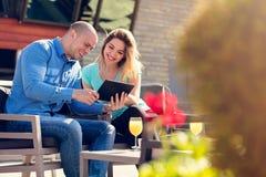 Νέοι ζεύγος, γυναίκα και άνδρας, στον καφέ και το χυμό κατανάλωσης καφέδων οδών προσέχοντας τις εικόνες των διακοπών στοκ εικόνα