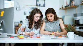 Νέοι θηλυκοί αρχιτέκτονες που συζητούν με το σχεδιάγραμμα στην αρχή απόθεμα βίντεο