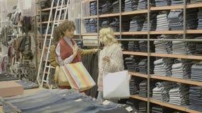 Νέοι θηλυκοί φίλοι που ψάχνουν τα δώρα φίλων για την ημέρα βαλεντίνων στη λεωφόρο κρατώντας τις τσάντες αγορών στα χέρια τους - φιλμ μικρού μήκους