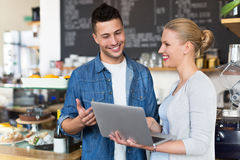 Νέοι ιδιοκτήτες καφέδων που εξετάζουν το lap-top στοκ φωτογραφίες