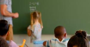 Νέοι καυκάσιοι αρσενικοί δάσκαλος και μαθήτρια που λύνουν math το πρόβλημα στον πίνακα κιμωλίας 4k φιλμ μικρού μήκους