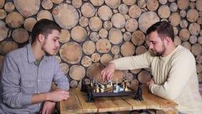Νέοι καυκάσιοι αρσενικοί φίλοι που παίζουν ένα παιχνίδι του σκακιού μαζί στο σπίτι Υπόβαθρο πλαισίων Woodem φιλμ μικρού μήκους