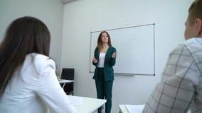 Νέοι καυκάσιοι προγυμνάζοντας φοιτητές πανεπιστημίου δασκάλων whiteboard πλησίον στην τάξη απόθεμα βίντεο