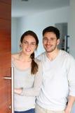 Νέοι καλωσορίζοντας φιλοξενούμενοι ζευγών στη μπροστινή πόρτα Στοκ φωτογραφίες με δικαίωμα ελεύθερης χρήσης