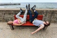Νέοι κουρασμένοι φίλοι ανθρώπων που χαλαρώνουν στον πάγκο Στοκ εικόνα με δικαίωμα ελεύθερης χρήσης