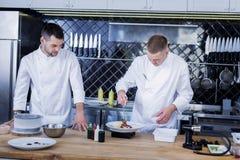 Νέοι μάγειρες που εργάζονται στην κουζίνα από κοινού στοκ εικόνα με δικαίωμα ελεύθερης χρήσης