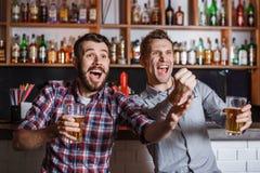 Νέοι με το ποδόσφαιρο προσοχής μπύρας σε έναν φραγμό Στοκ φωτογραφία με δικαίωμα ελεύθερης χρήσης