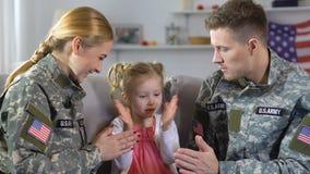 Νέοι μητέρα και πατέρας στο κτύπημα-α-κέικ παιχνιδιού στρατιωτικών στολών με την κόρη φιλμ μικρού μήκους