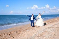 Νέοι νύφη και νεόνυμφος που περπατούν στην ακτή στοκ φωτογραφίες
