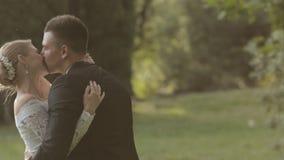 Νέοι νύφη και νεόνυμφος που φιλούν και που γελούν μέσα φιλμ μικρού μήκους
