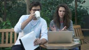 Νέοι ομο εργαζόμενοι που εργάζονται στο θερινό καφέ με το lap-top και την περιοχή αποκομμάτων απόθεμα βίντεο