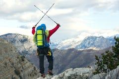 Νέοι ορεσίβιοι που στέκονται με το σακίδιο πλάτης πάνω από ένα βουνό Στοκ Εικόνα