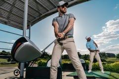 Νέοι παίκτες γκολφ με τις λέσχες που παίζουν το γκολφ από κοινού Στοκ εικόνες με δικαίωμα ελεύθερης χρήσης