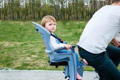 Νέοι πατέρας και κόρη που οδηγούν ένα ποδήλατο στο πάρκο Στοκ Φωτογραφία